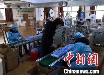 浏阳市政协委员、长沙芙蓉口罩厂厂长伍海湾(中)与工人们一起加班加点生产口罩。湖南省政协供图