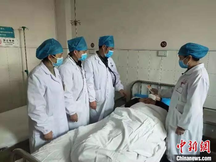 湖南省政协委员、衡阳市中医医院院长王诚喜(左三)在病房查看患者情况。湖南省政协供图